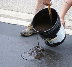 pouring asphalt sealer armor coat on driveway