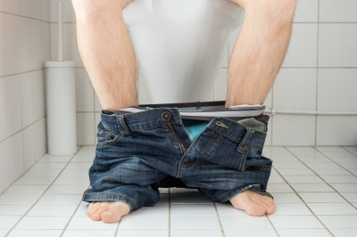 man in small bathroom toilet with pants pulled down