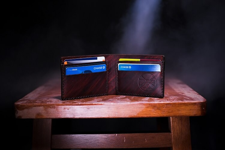 mans wallet filled with credit cards
