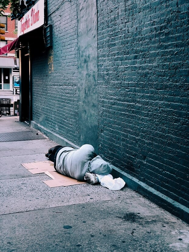Financial difficulty homeless sleeping against a wall