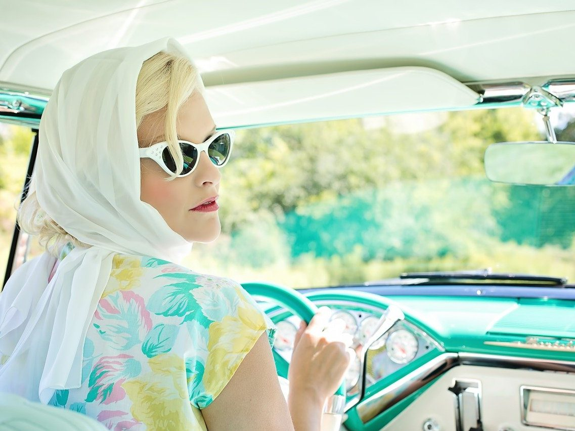 Blonde woman with white sunglasses in a vintage car.