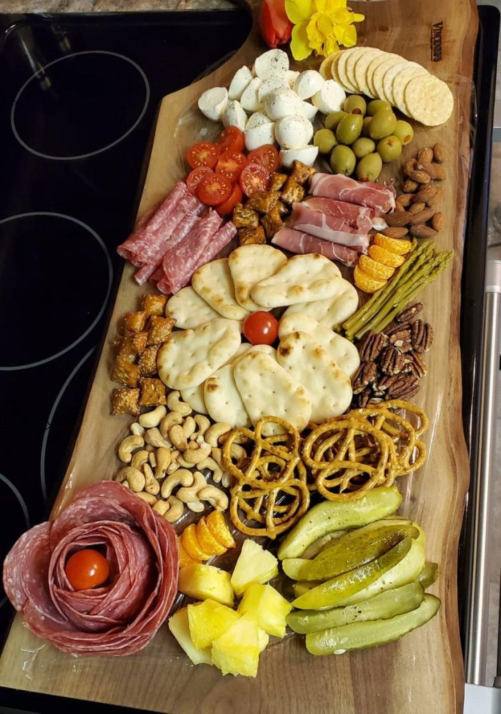 An Italian Charcuterie Board filled with meats, cheeses, nuts, olives, and pickled foods and vegetables.