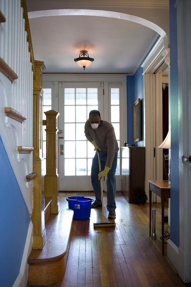 Man mopping the floor. Sharing the chores using a weekly cleaning schedule.