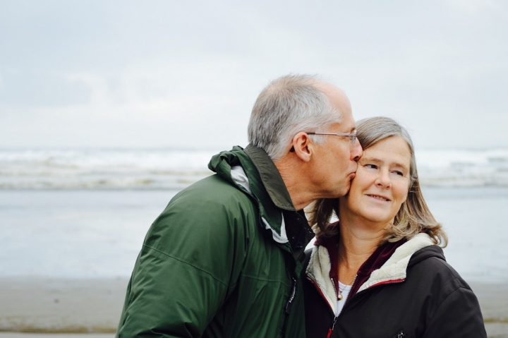Senior couple at the beach standing in the sand.