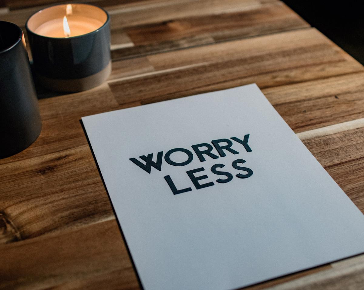 How to worry less about your financial situation by doing something about it. Piece of white paper on a desk with candles that states Worry Less.
