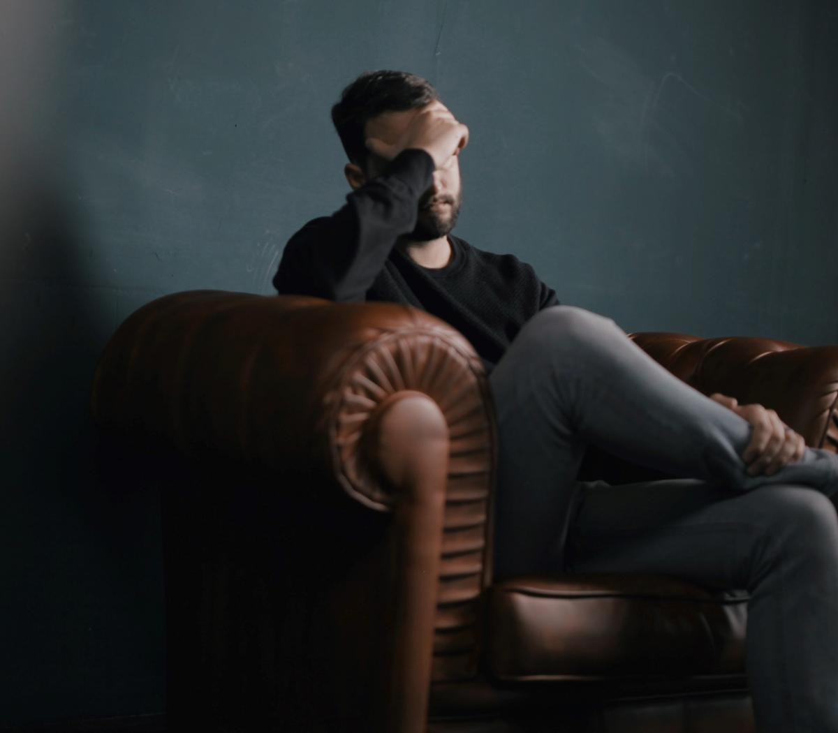 How To Reduce Financial Worries Once And For All. A man sitting on a leather couch in deep thought.